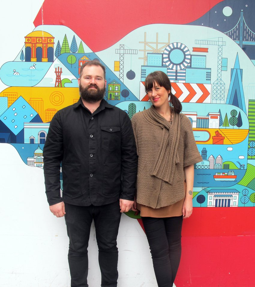 A bearded man and a woman stand in front of a colorful image