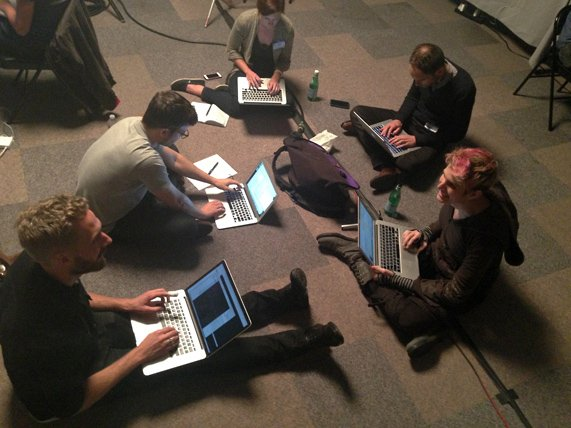 A group sitting on the floor, working on laptops