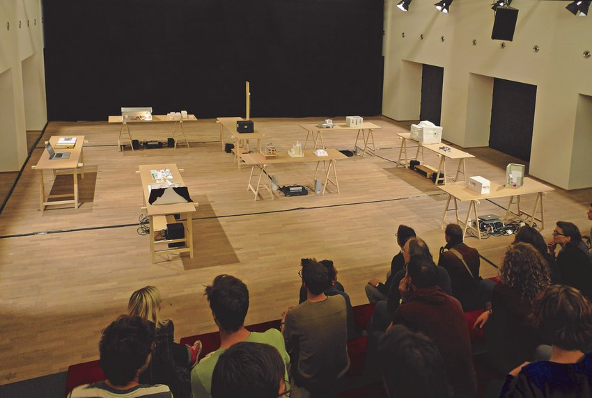 An auditorium filled with viewers and white boxes arranged on a stage, Soundtracks