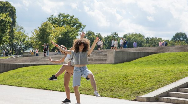 two women dancing with arms and legs up in public park