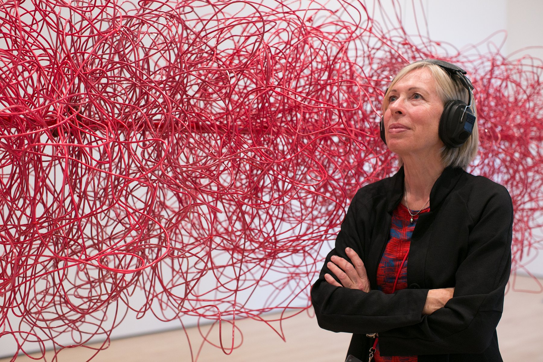 A blond Caucasian woman wears black headphones next to a cloud made of red electrical wires, Kubisch, Soundtracks