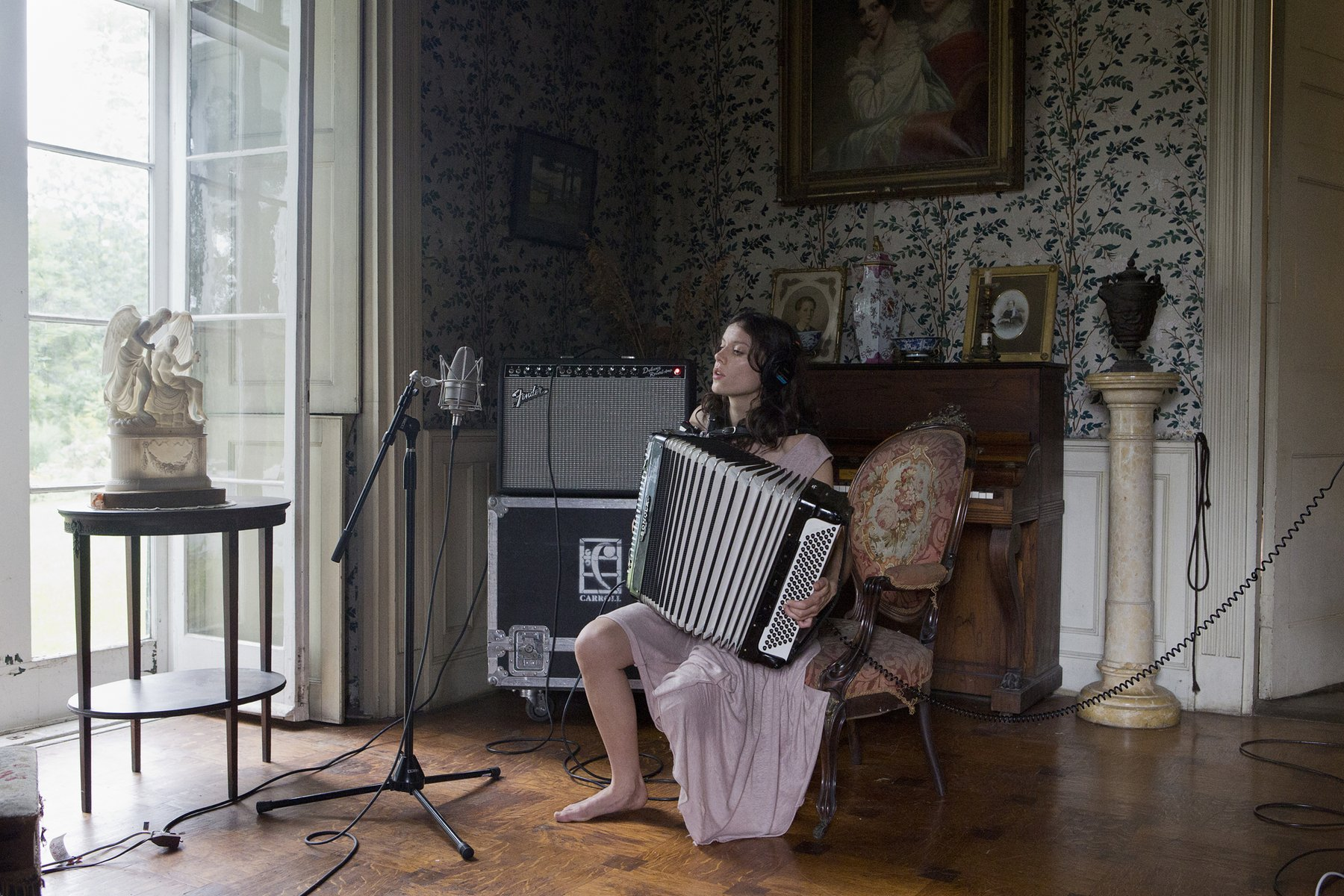 A woman in headphones sits alone playing an accordion in an ornately decorated but slightly ramshackle drawing room