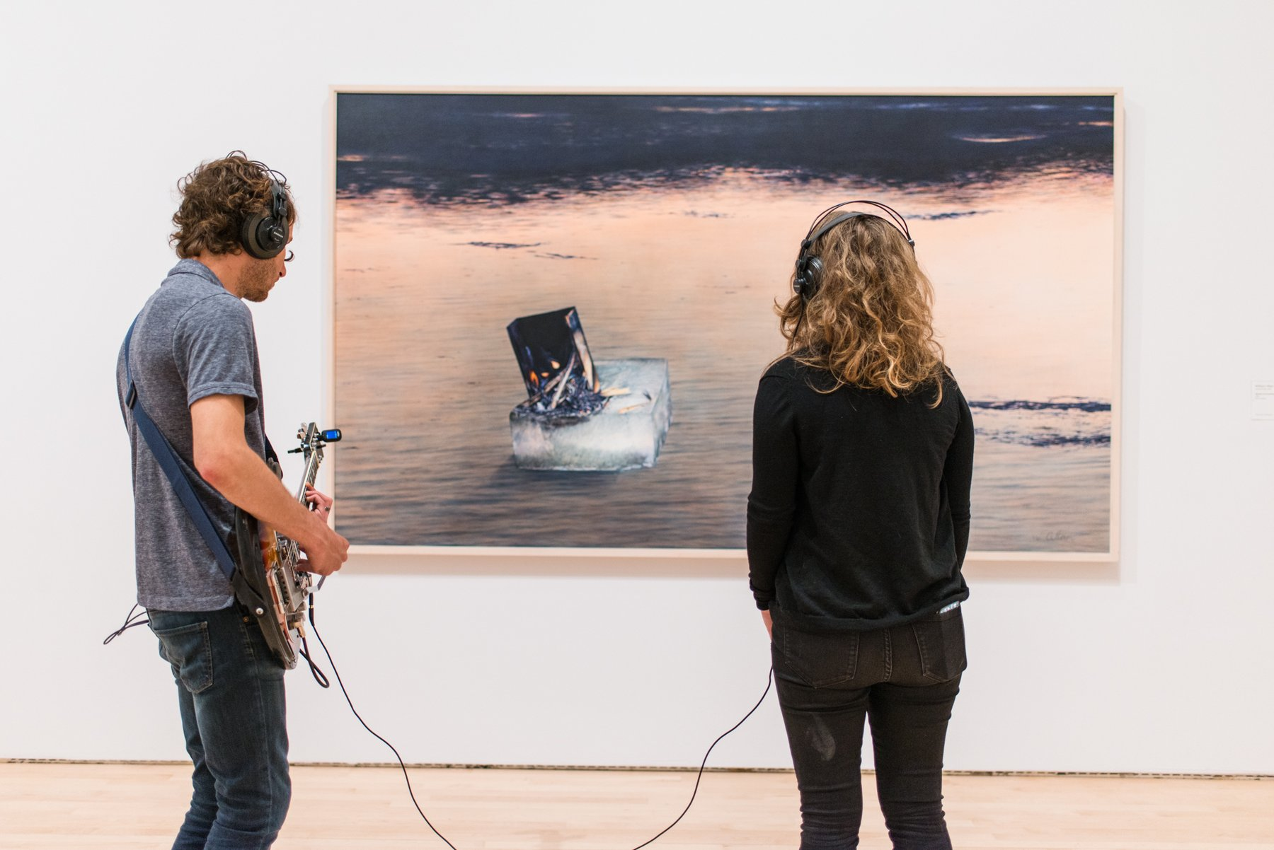 A man playing guitar stands next to a woman listening on headphones in front of a painting, Kallmyer/Allen, Soundtracks