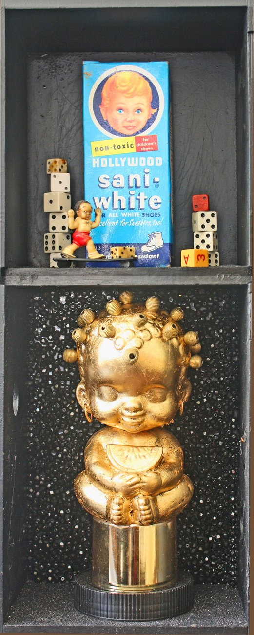 small gold statue in black box with packaging and dice