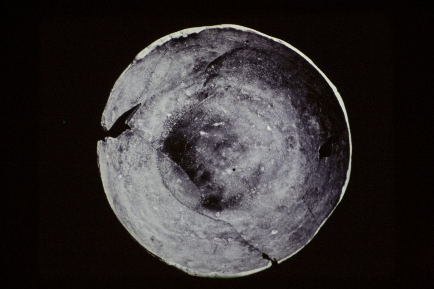 A grey circle resembling a broken plate on a black background