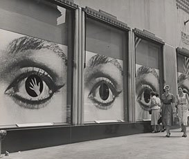 three large city windows covered with image of woman's eye; two women walking by windows in corner