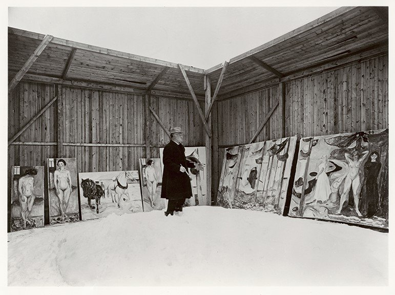 A black and white photograph of a Caucasian man in the snow surrounded by paintings