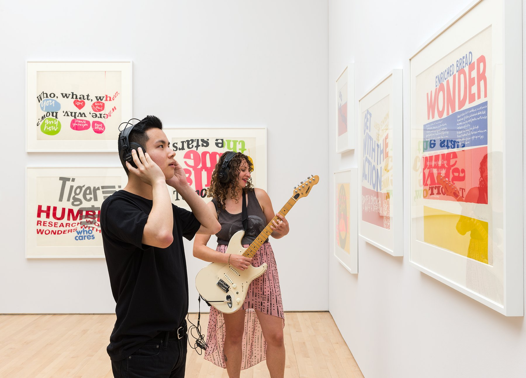 A Caucasian woman plays guitar while an Asian man listens wearing headphones in a gallery, Kallmyer/Allen, Soundtracks