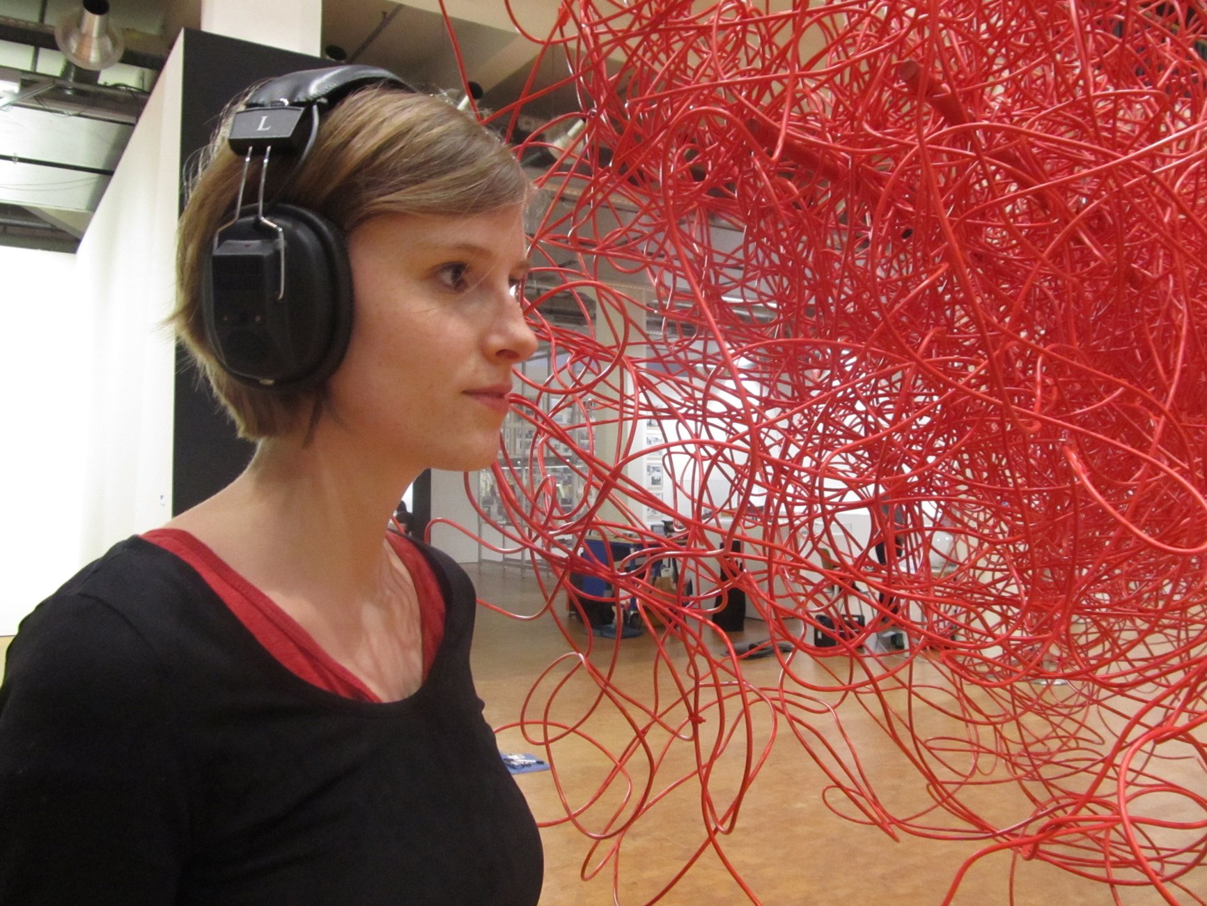 A woman in headphones stands listening next to a tangled, hanging mass of red cables