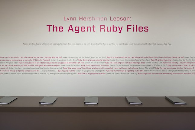 pink and black text on wall with five gray binders on counter (Agent Ruby Files installation shot)