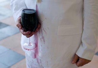 Dennis Adams, man holding wine glass spilling on white coat