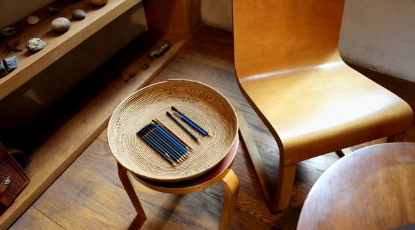 pencils lined up in a basket on a wooden stool, next to a wooden chair