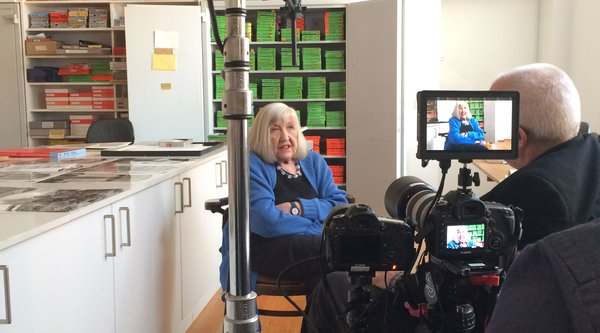 A behind-the-scenes shot of a white-haired woman being interviewed on video