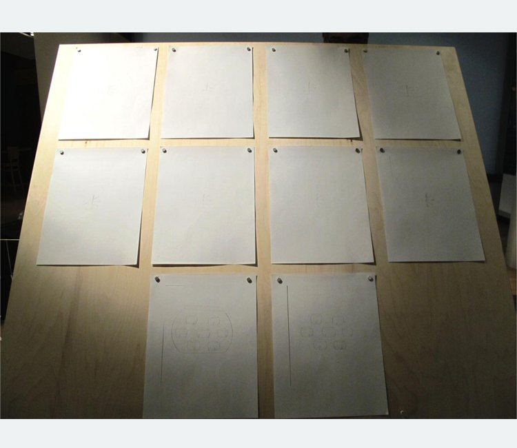 Ten hand drawings on white paper tacked to a wooden board