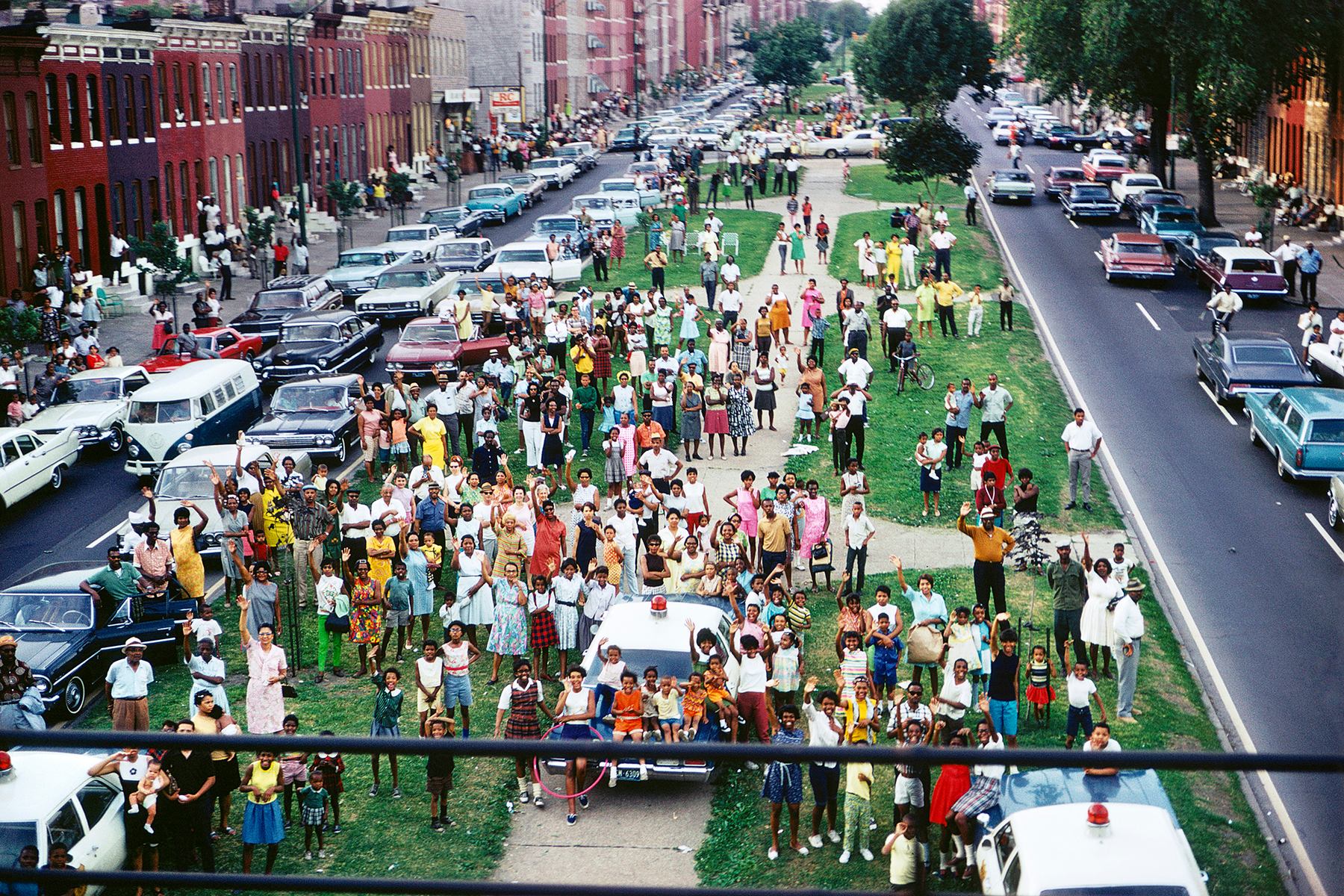A large group of people standing on a grassy median in a city waving toward the camera