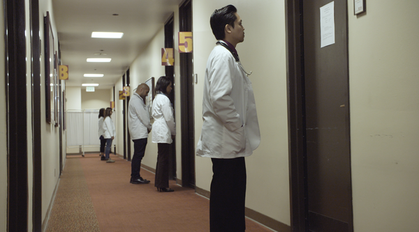 A row of doctors in white coats stand outside doors along a corridor