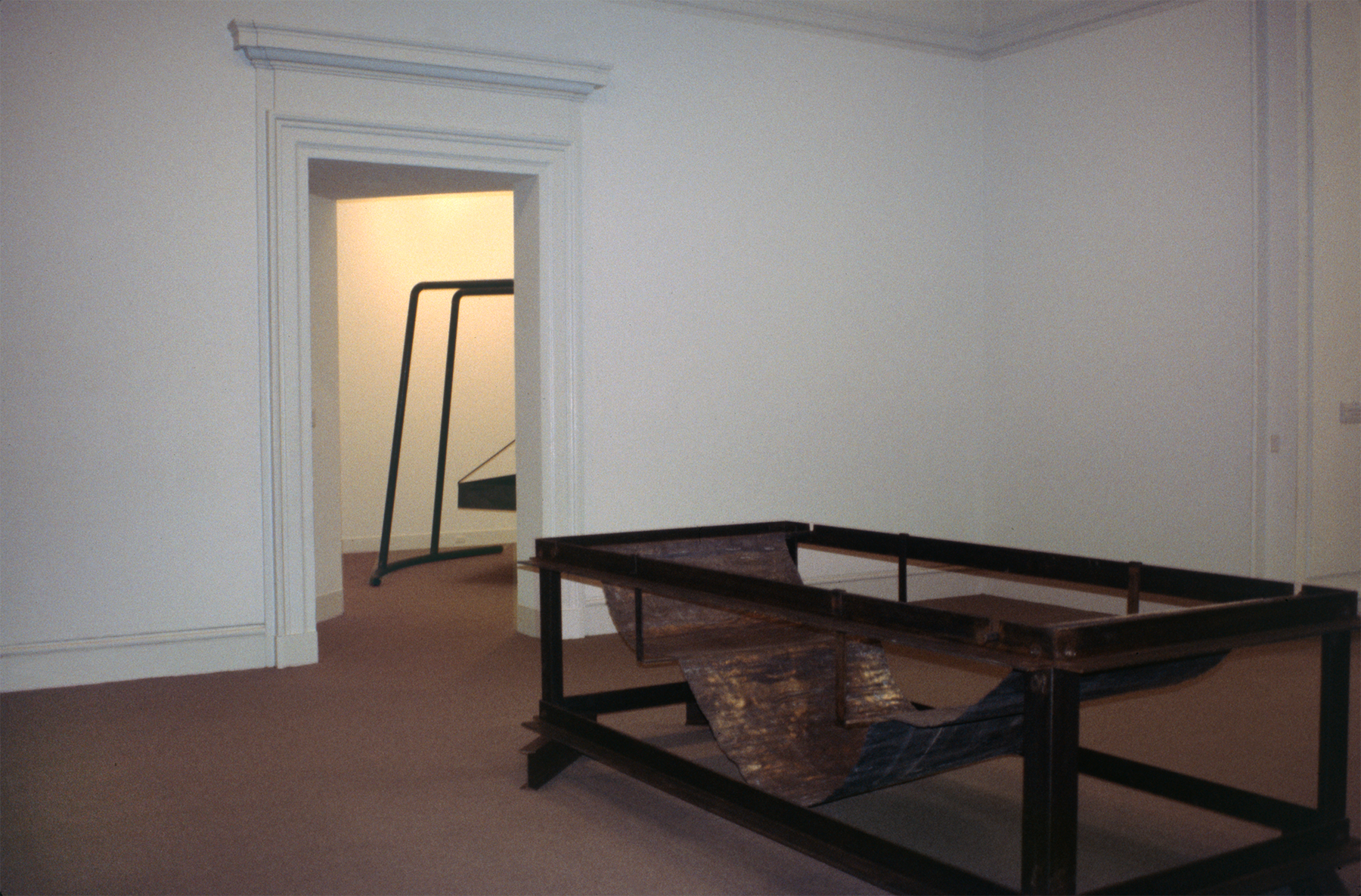A large, rusted metallic sculpture in a gallery