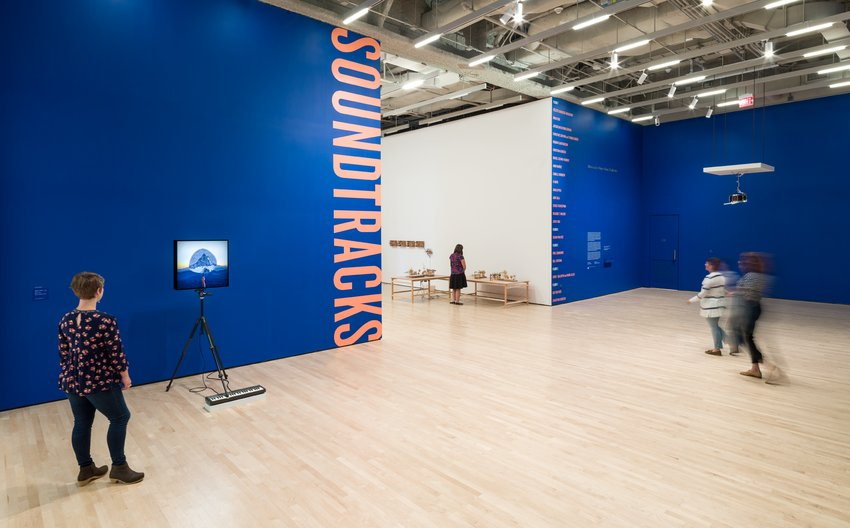 A gallery entrance with blue walls and the word Soundtracks written vertically