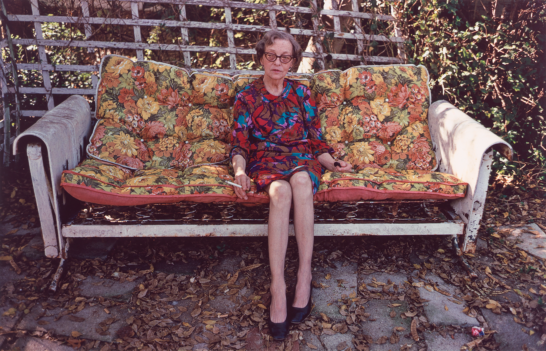An elderly seated woman smoking a cigarette on a worn out floral print couch in an unkempt patio