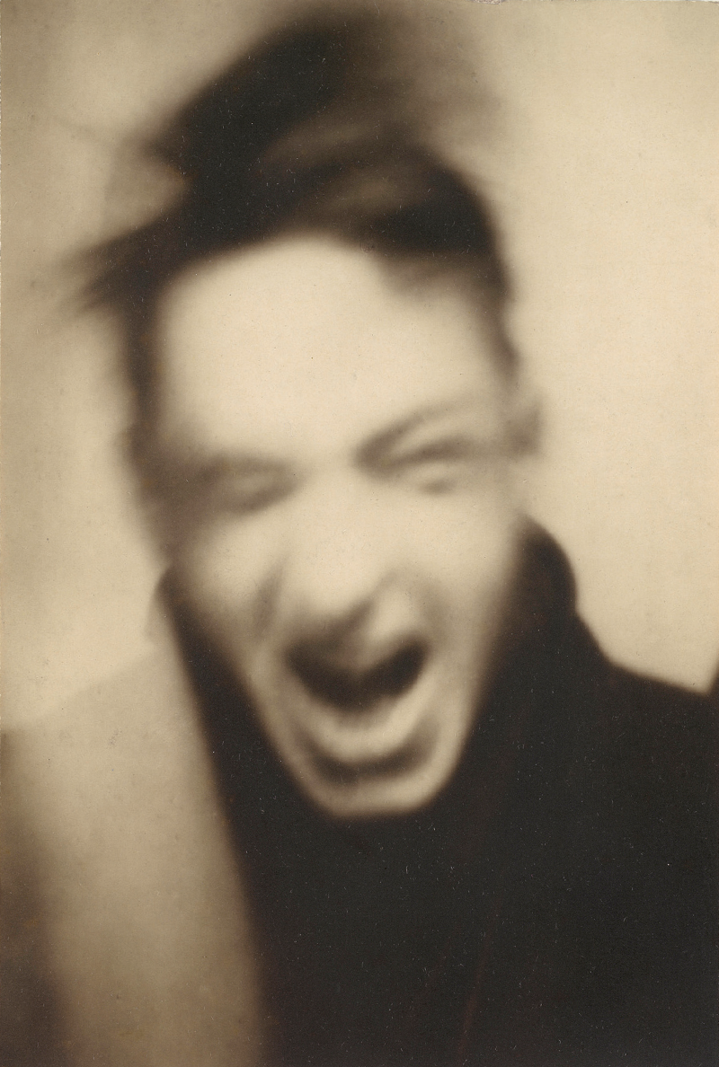 A blurry black and white photograph of a screaming man with disheveled hair