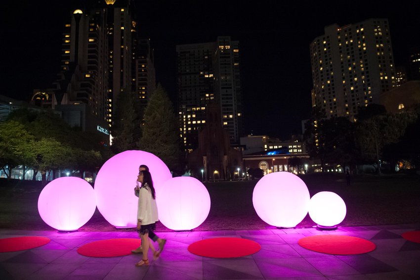 A couple walks in front of a series of glowing balls, Gatti