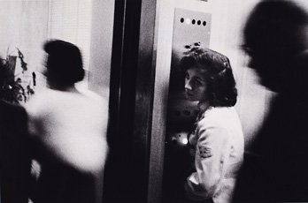 Robert Frank, woman leaning against elevator door with two blurry figures