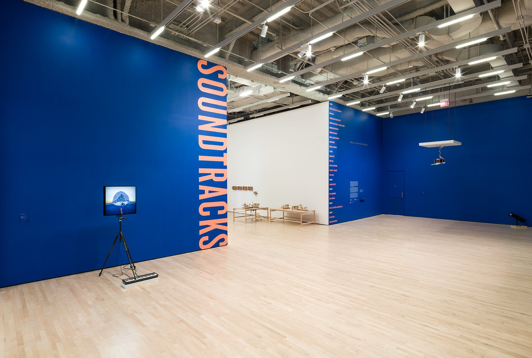 A video screen on a tripod before a blue wall with the words soundtracks written in orange vertically, Walker, Soundtracks