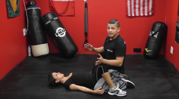 A man sits over a woman on her back in a red work-out room