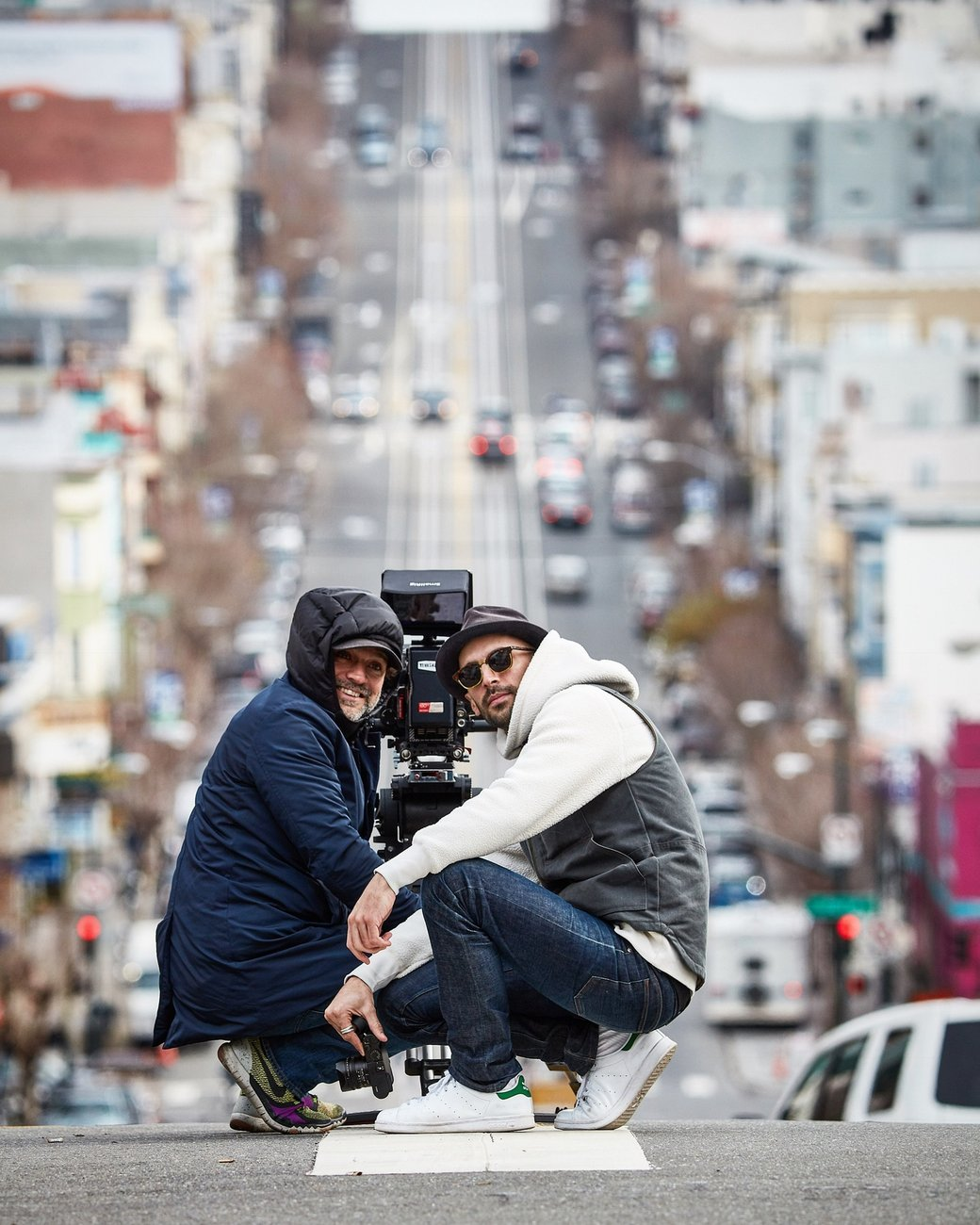two people posing for a photograph on a sloped city street