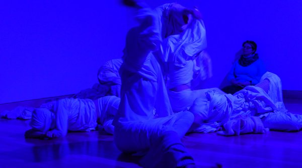 multiple people doing a performance in blue lit room