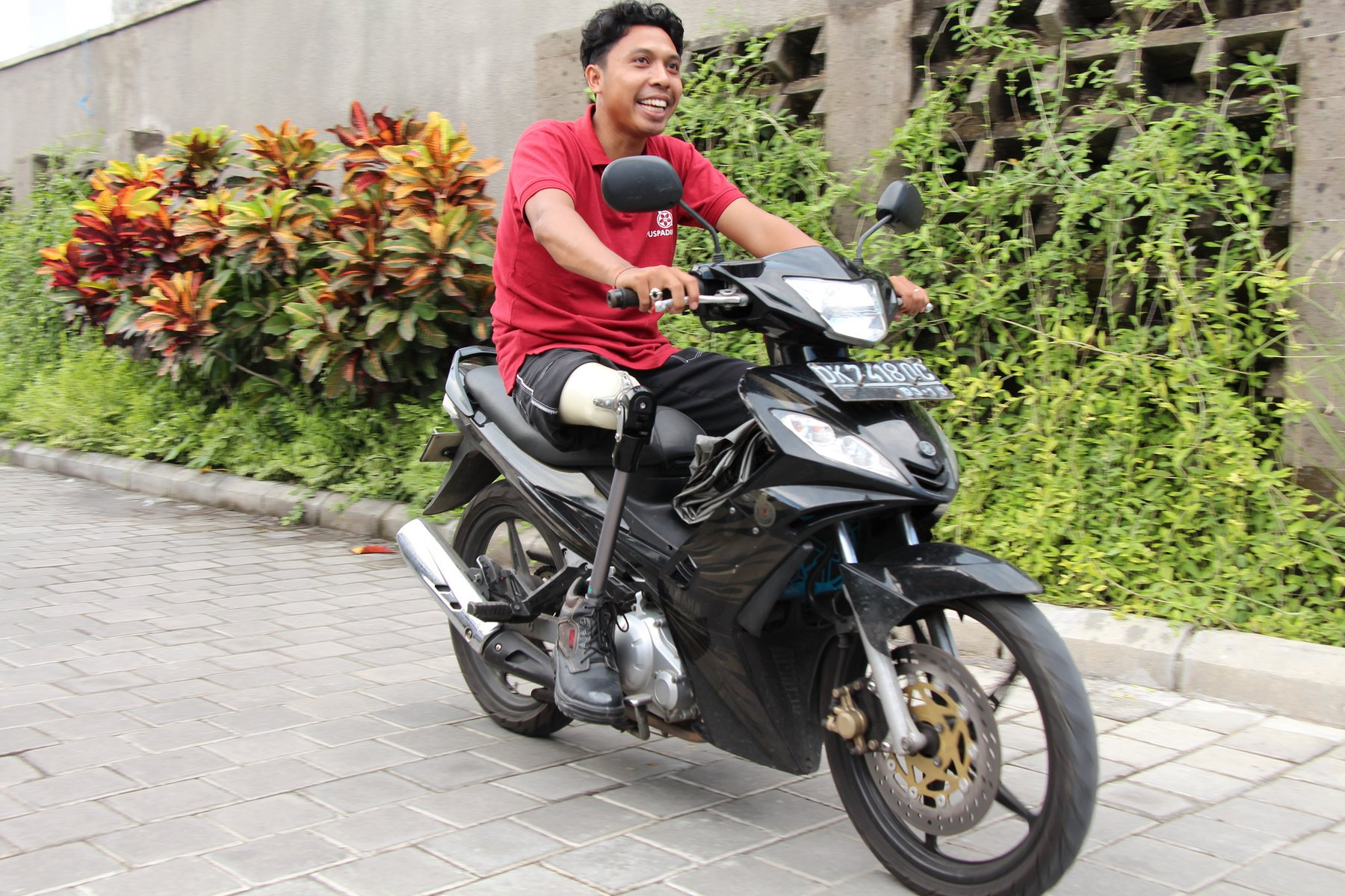 A man in a red t-shirt on a motorbike parked in a plant-lined paved driveway