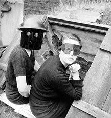 photograph of two women sitting in cellar door wearing fire masks