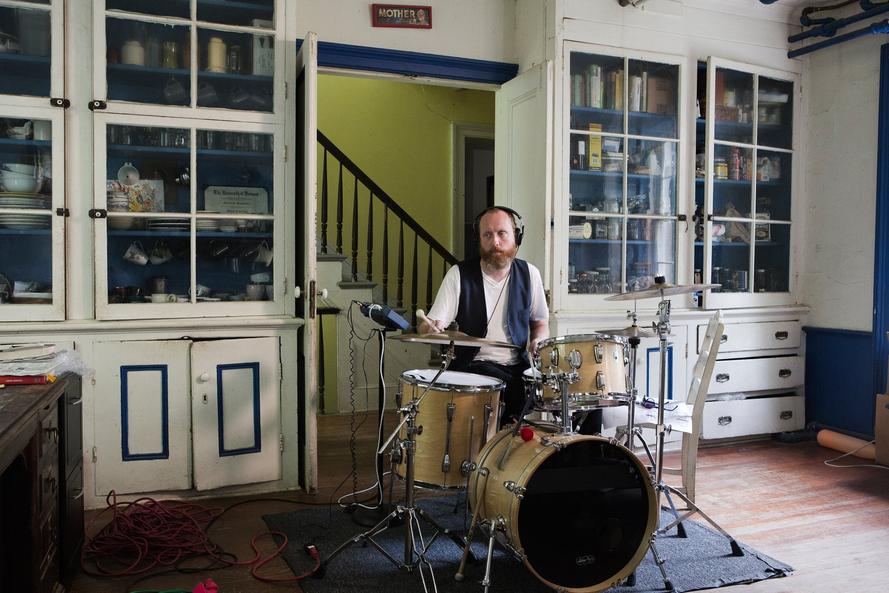 A bearded Caucasian man wearing a blue vest plays a drum set in a domestic living room, Kjartansson