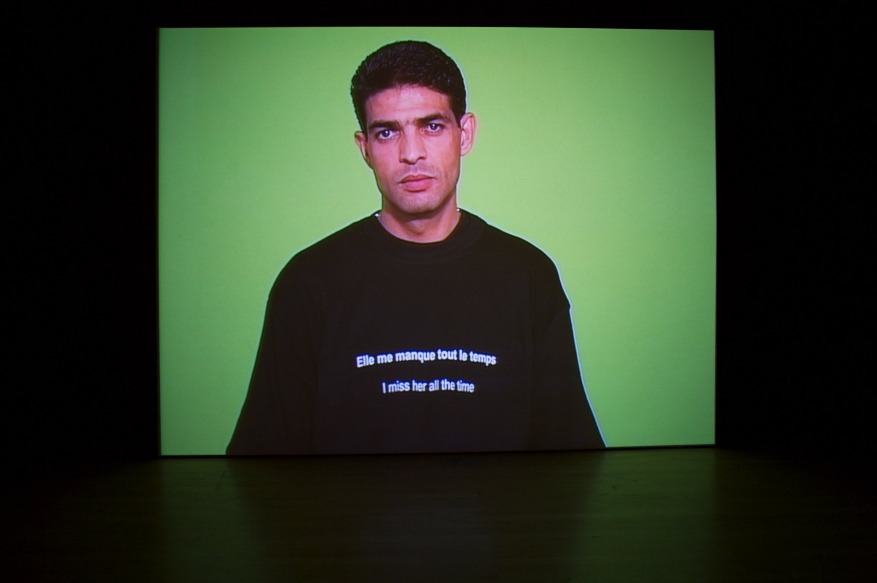 "An image of a man in front of a green wall wearing a sweatshirt that says ""I miss her all the time"" in both English and French"