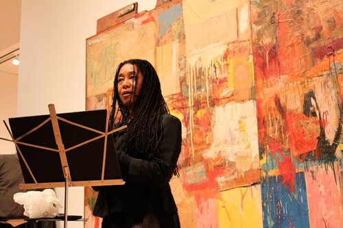 A woman speaks in front of a colorful artwork.