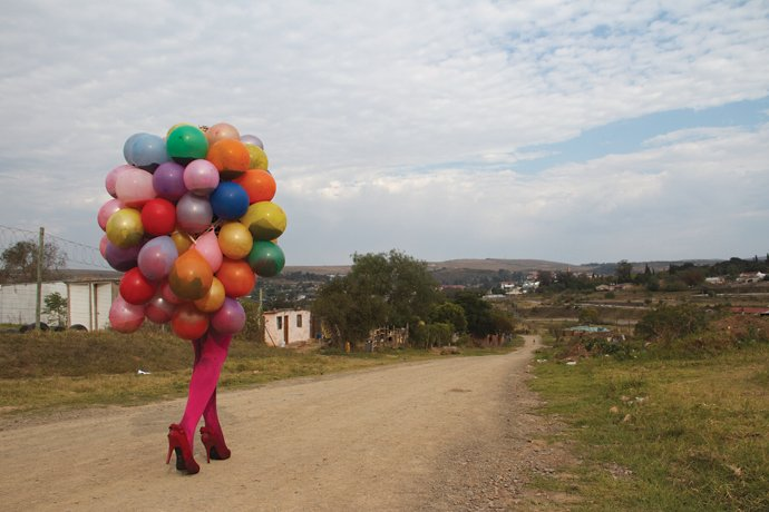colorful balloons and legs in pink stockings walking down dirt path