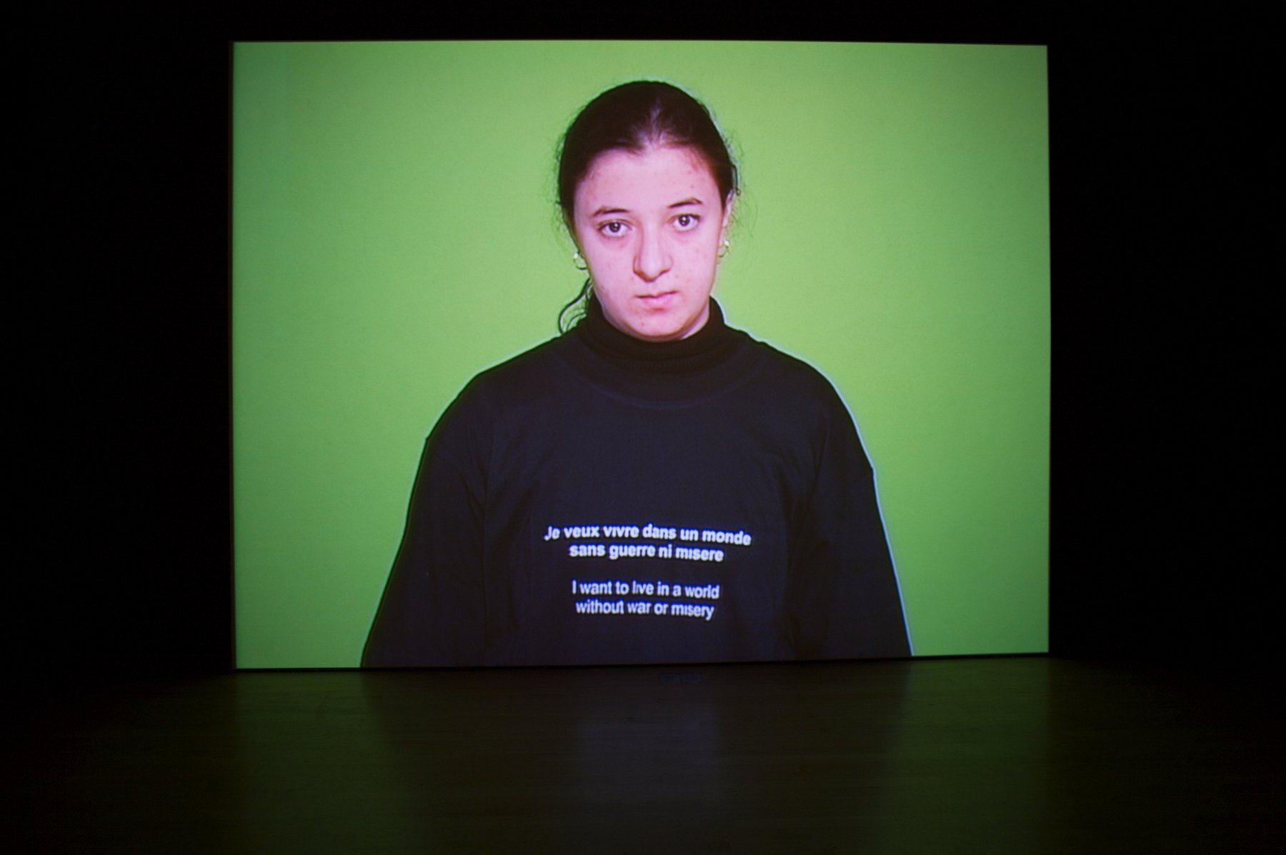 "An image of a woman in front of a green background wearing a sweatshirt that says ""I want to live in a world without war or misery"" in both English and French"