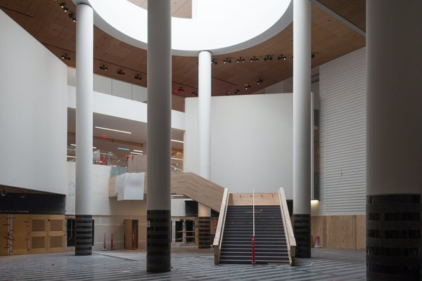 A crooked staircase winds up a columned atrium