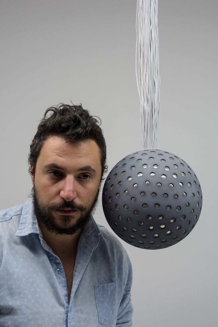 A Caucasian man with dark hair and beard listens to a perforated hanging sphere, Lozano-Hemmer Soundtracks