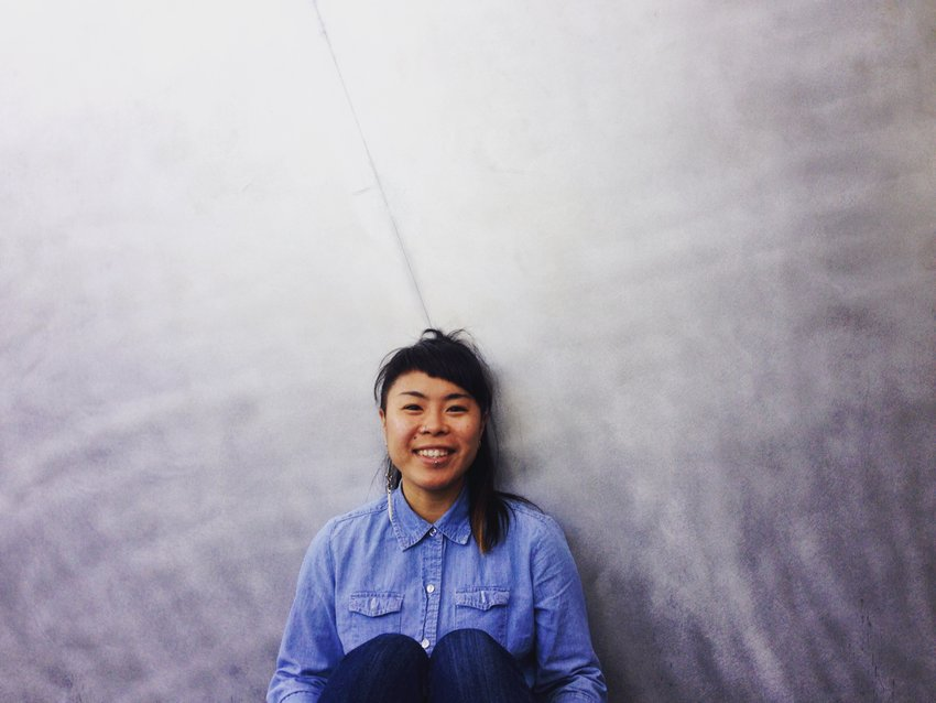 An Asian-American woman with bangs and wearing a denim shirt sits before a gradated grey background, Geraldine Ah-Sue