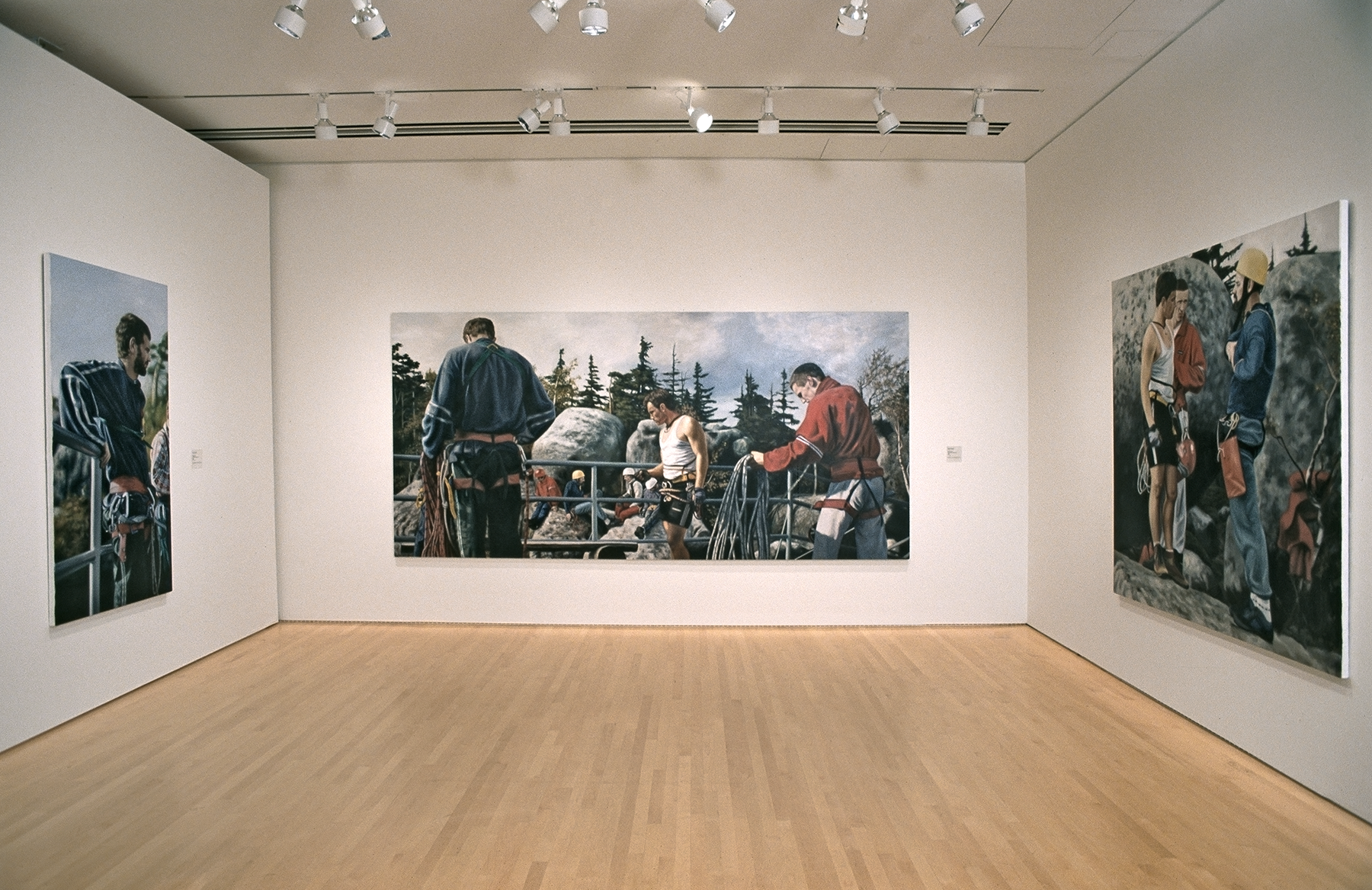 Room featuring three large paintings of rock climbers