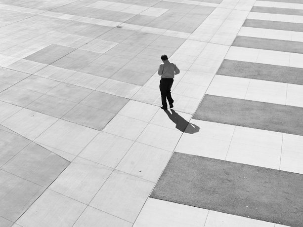 man walking on gridded pavement