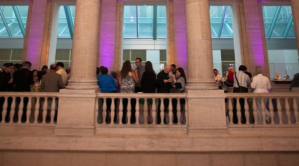 A group of people mingle and eat on a museum balcony