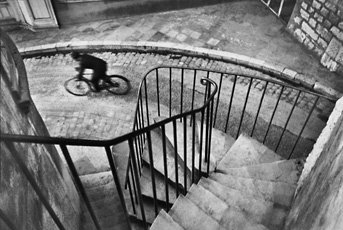 Cartier-Bresson, perspectival photo of stairwell leading to man on bicycle on street