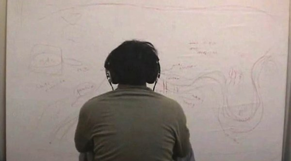 A man in headphones sits before a white canvas