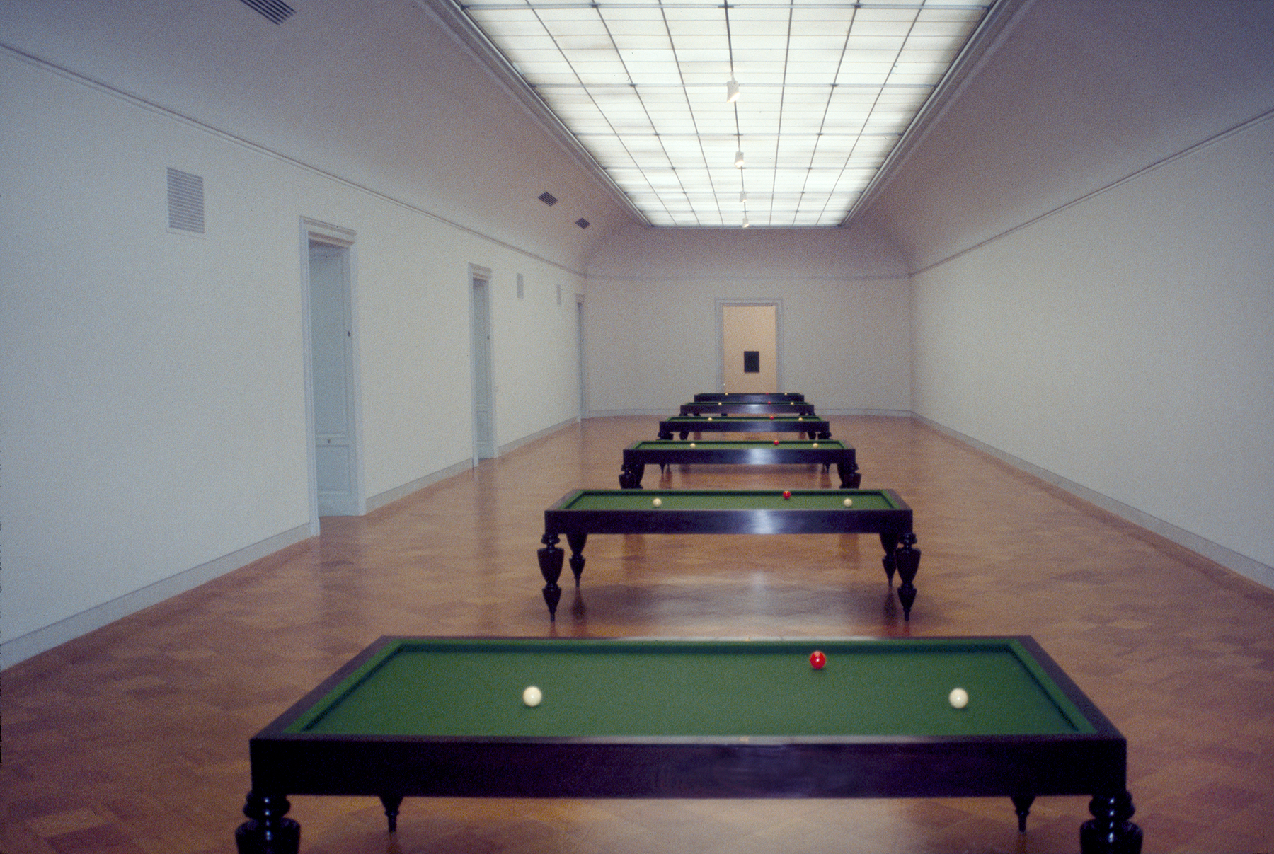 five billiards tables standing in a row with two white balls and one red ball placed in the same position on each
