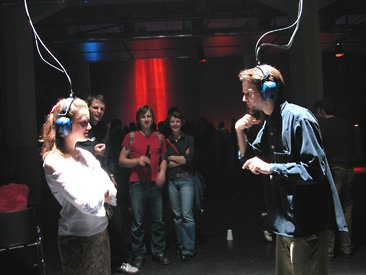 Gommel, installation view of woman and man looking at each other wearing headphones