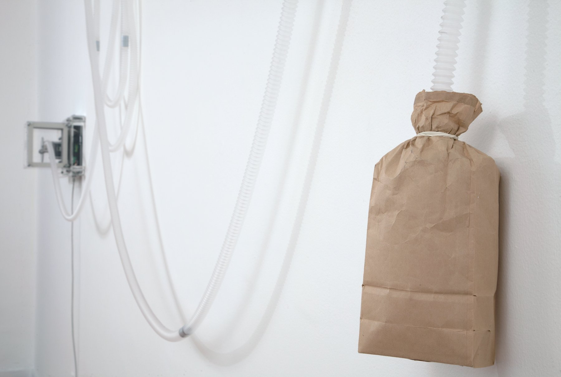 A brown paper bag tied with string hangs on a white wall, Lozano-Hemmer Soundtracks