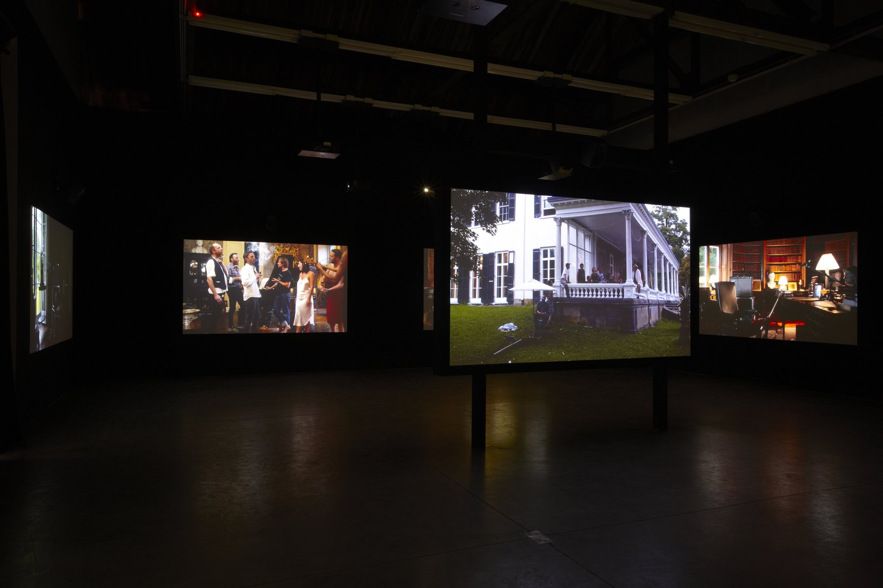A darkened gallery is illuminated by several floor to ceiling video screens, installation view Kjartansson