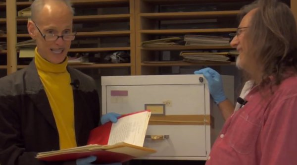 John Waters holds a red folder